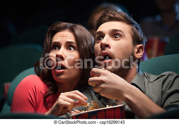 Horror movie. Terrified young couple eating popcorn while watching movie at the cinema - csp16299143