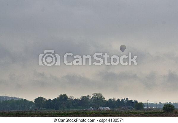 Hot Air Balloon Flying on a Foggy Morning - csp14130571