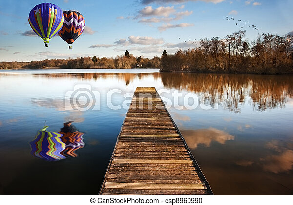 Hot air balloons over sunset lake with jetty - csp8960990