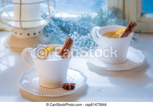 Hot and aromatic tea with orange and cinnamon for Christmas - csp61473644