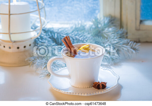 Hot and sweet tea with cinnamon and orange for Christmas - csp61473648