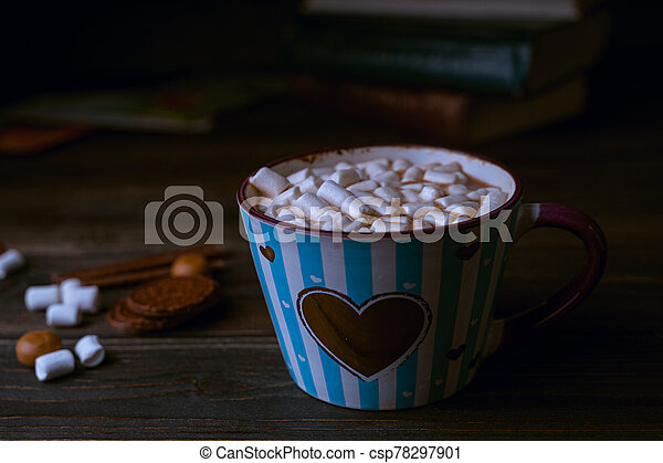 Hot chocolate drink with marshmallows in blue striped cup, stacked books on wooden rustic background. Closeup view - csp78297901