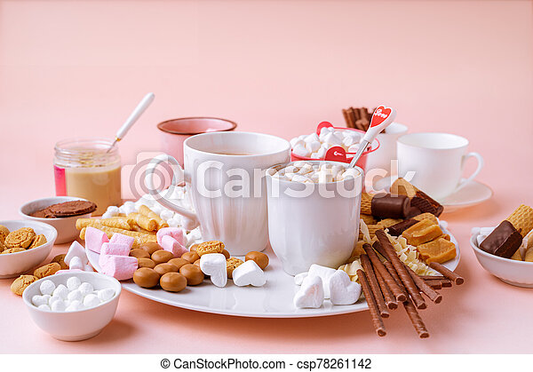 Hot chocolate in mugs, marshmallows, chocolates and cookies on pink background - csp78261142