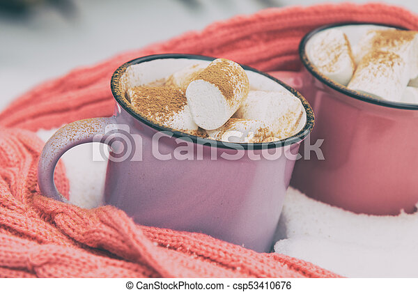 Hot chocolate with marshmallow in pink and violet two cups wrapped in a cozy winter pink scarf on the snow-covered table in the garden. Coloring and processing photo small depth of field - csp53410676
