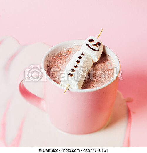 Hot cocoa with marshmallow snowman in a pink mug on a pink background - csp77740161