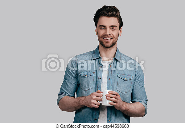 268991eb6c1 Hot Coffee For Hot Man. Handsome Smiling Young Man In Blue Jeans Shirt  Holding A Cup And Looking At