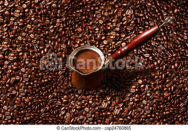 Hot coffee prepared in a Turk. Top view on beautiful foam with coffee beans background. - csp24760865