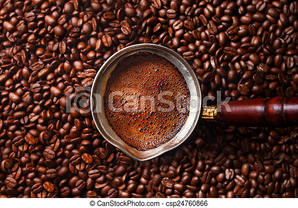 Hot coffee prepared in a Turk. Top view on beautiful foam with coffee beans background. - csp24760866