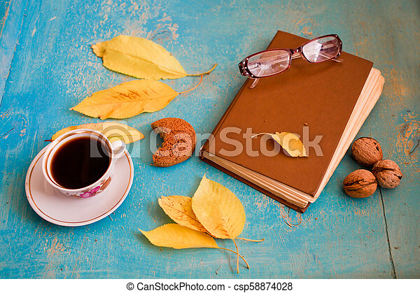 Hot coffee, vintage book, glasses and autumn leaves on wood background - relax or retirement concept - csp58874028