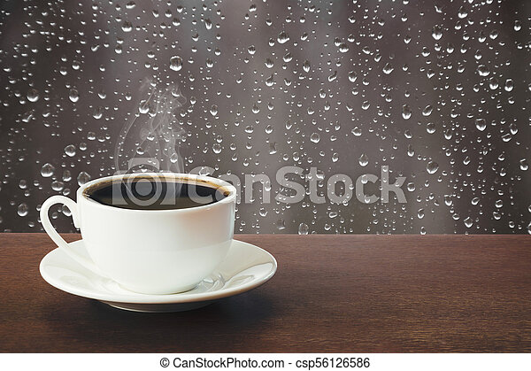 Hot cup of black coffee in a rainy day on tabletop. - csp56126586