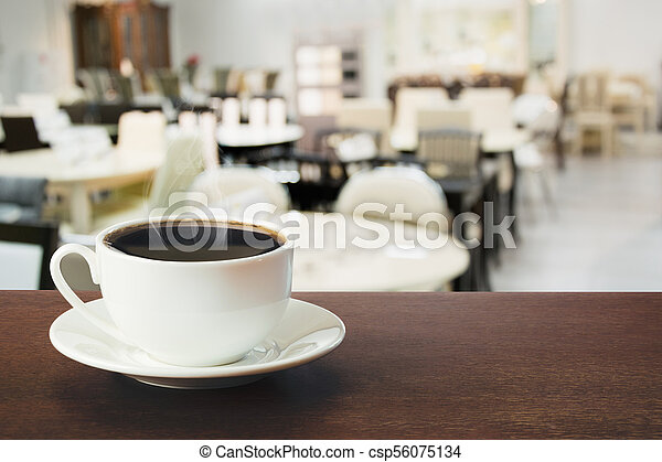 Hot cup of black coffee on tabletop in cafe. Indoors. - csp56075134