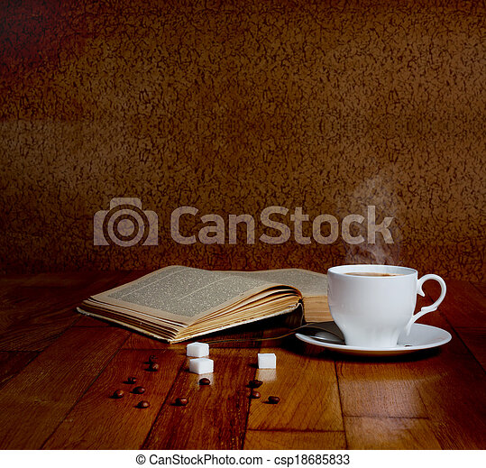 Hot cup of fresh coffee on the wooden table and a stack of books to read - csp18685833