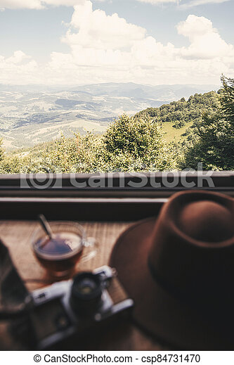 Hot tea in glass cup and hipster hat on background of  beautiful landscape of woods and mountains. View from wooden window, focus on mountain. Space for text. Travel and vacations - csp84731470
