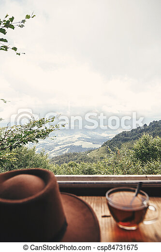 Hot tea in glass cup and hipster hat on background of  beautiful landscape of woods and mountains. View from wooden window on mountain. Space for text. Travel and vacations - csp84731675