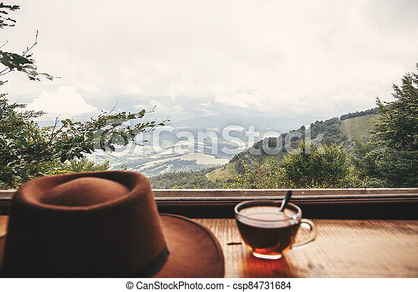 Hot tea in glass cup and hipster hat on background of  beautiful landscape of woods and mountains. View from wooden window on mountain. Space for text. Travel and vacations - csp84731684