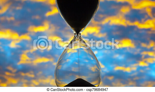 Hourglass against the sunset bright sky. Time and implementation of plans - csp79684947