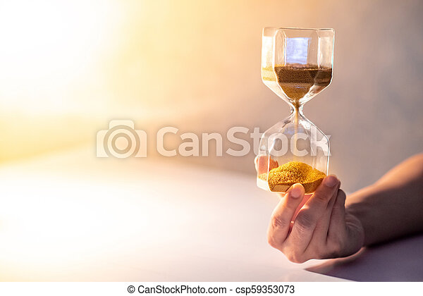 Hourglass on male hand, Time passing concept - csp59353073