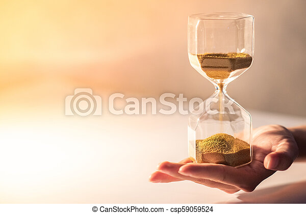 Hourglass on male hand, Time passing concept - csp59059524