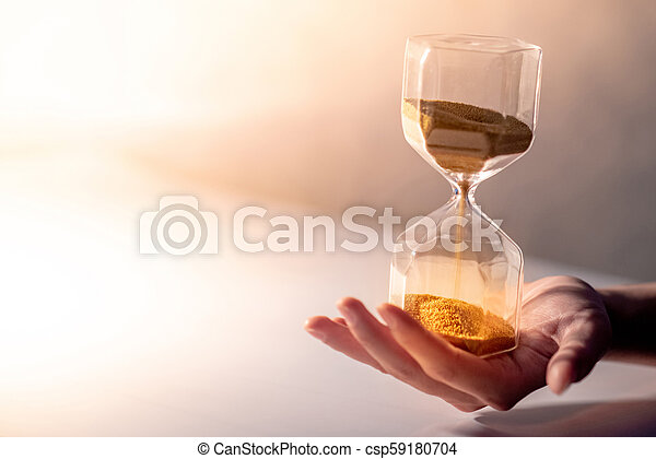 Hourglass on male hand, Time passing concept - csp59180704