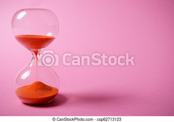 Hourglass with orange sand on pink background. - csp62713123