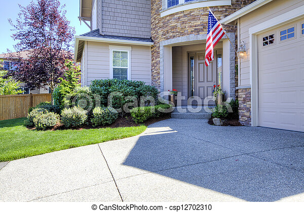 House exterior with driveway and American flag. - csp12702310