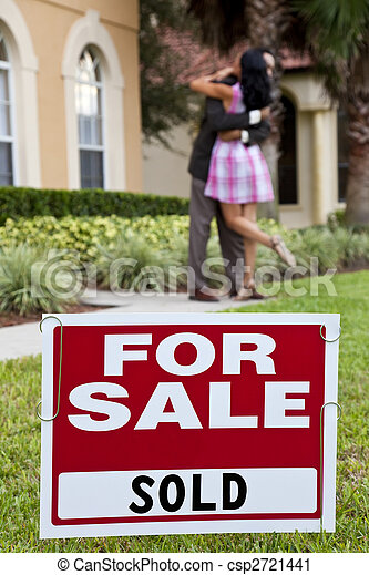 House For Sale and Sold sign with African American couple celebrating the purchase of a house out of focus behind the sign. - csp2721441