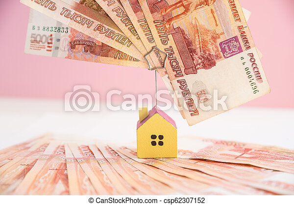 house model set on banknote for concept investment mortgage fund finance and home loan. Small wooden house on the background of russian banknotes. Symbolic image of buying or renting a house. - csp62307152