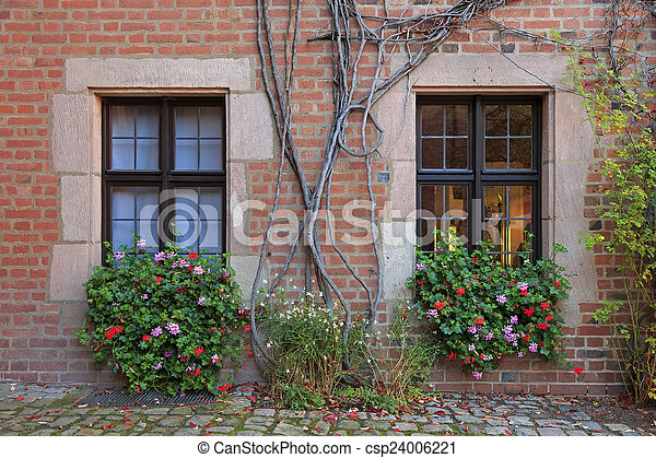 House windows with flowers, vines and brick wall in Nuremberg - csp24006221