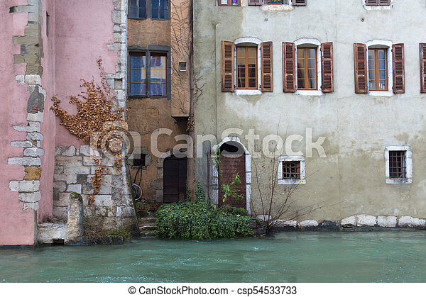 Houses of different colours, doors, windows and bushes near the river in Annecy, France - csp54533733