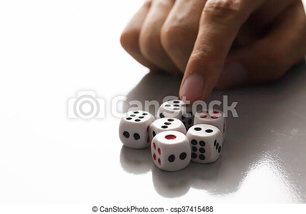 Human hand ready to roll the dice in very dark tone against the light - csp37415488