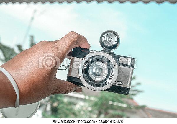 Human hands holding a camera - csp84915378