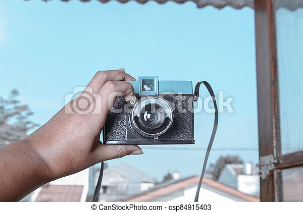 Human hands holding a camera - csp84915403