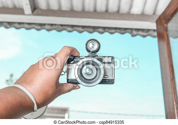 Human hands holding a camera - csp84915335