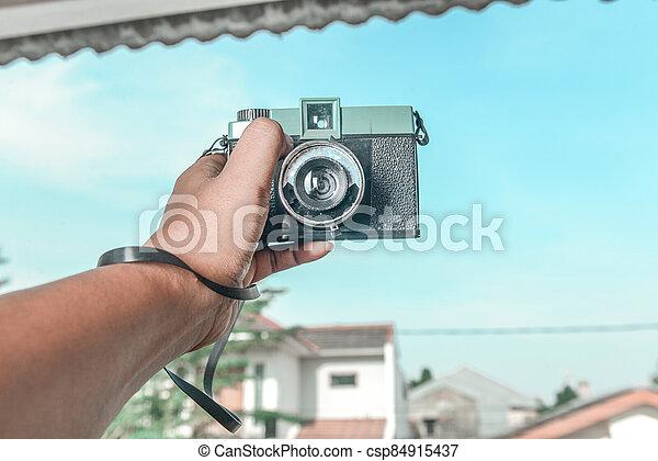 Human hands holding a camera - csp84915437