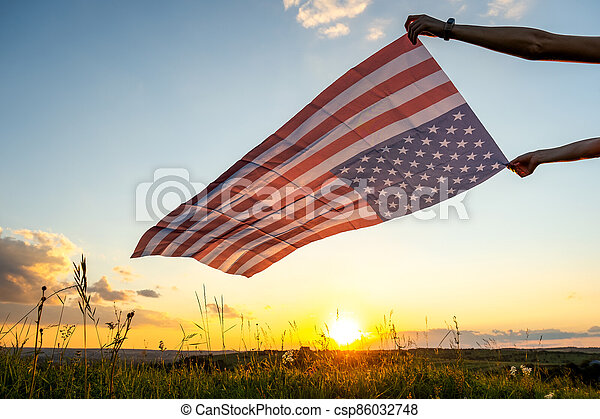 Human hands holding waving american national flag in field at sunset. - csp86032748