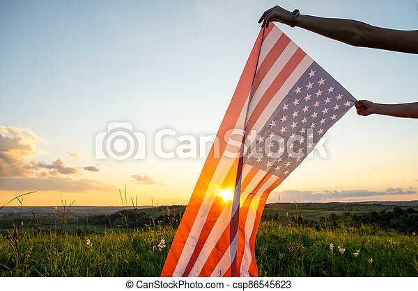 Human hands holding waving american national flag in field at sunset. - csp86545623