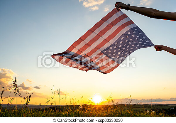 Human hands holding waving american national flag in field at sunset. - csp88338230