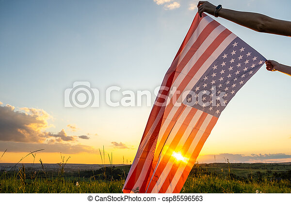 Human hands holding waving USA national flag in field at sunset. - csp85596563
