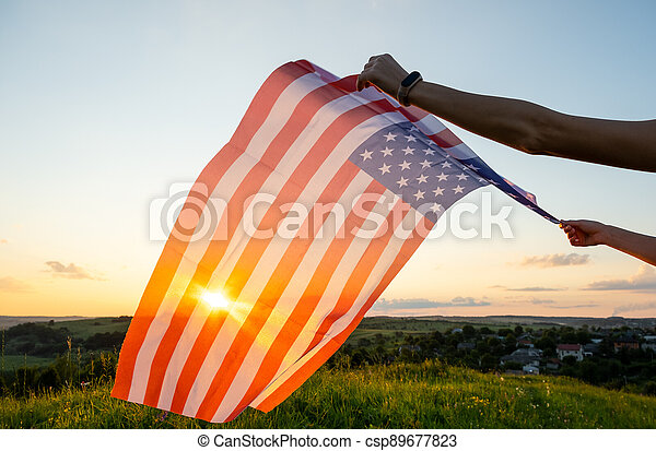 Human hands holding waving USA national flag in field at sunset. - csp89677823