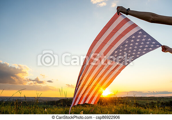 Human hands holding waving USA national flag in field at sunset. - csp86922906