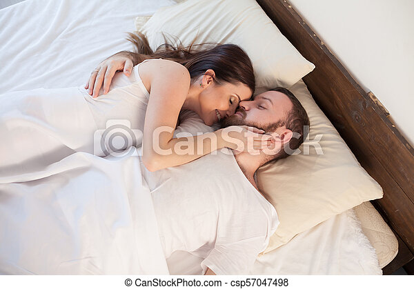 . husband and wife are sleeping in beds with white linen