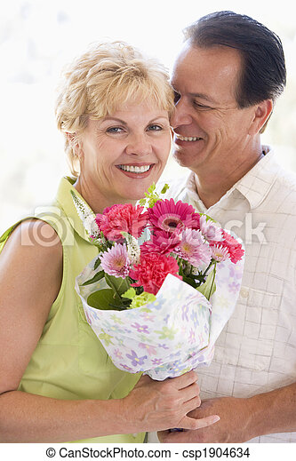 Husband and wife holding flowers and smiling - csp1904634