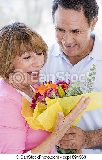 Husband and wife holding flowers and smiling - csp1894363