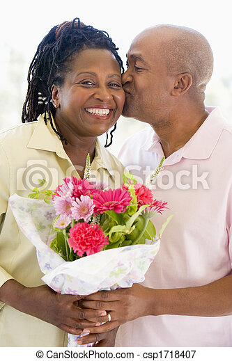 Husband and wife holding flowers kissing and smiling - csp1718407