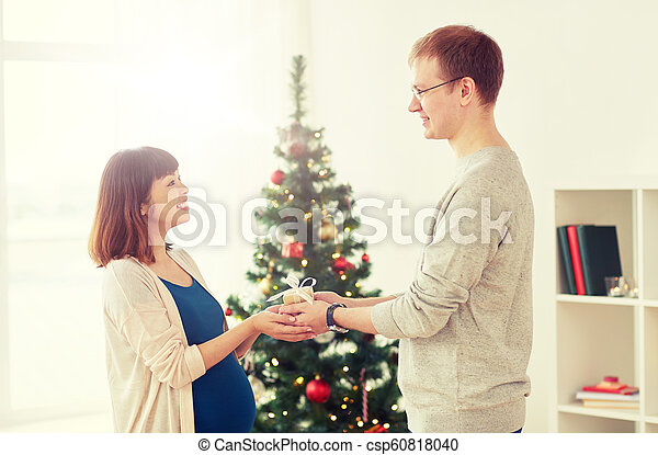 husband giving christmas present to pregnant wife csp60818040