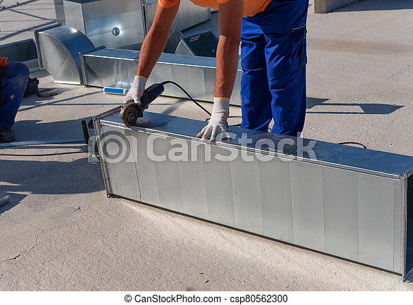 HVAC technician is working on a roof of new industrial building. Close-up view of the young technician repairing an air duct with the angle grinder. HVAC worker cutting ductwork with an angle grinder. - csp80562300