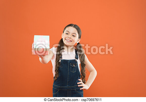 I love giving gifts. Cute small child giving a present box on orange background. Adorable little girl enjoy giving the gift. Giving and receiving, keeping it balanced - csp70697611