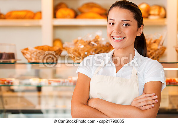 I love my job! Beautiful young woman in apron keeping arms crossed while standing in bakery shop - csp21790685