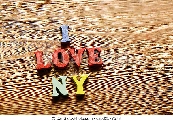 I LOVE NY- word made from multicolored letters on wooden background warm color