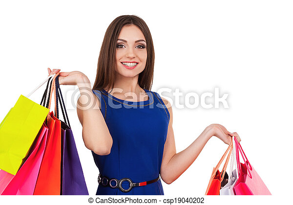 I need some retail therapy. Attractive young woman holding shopping bags and smiling at camera - csp19040202